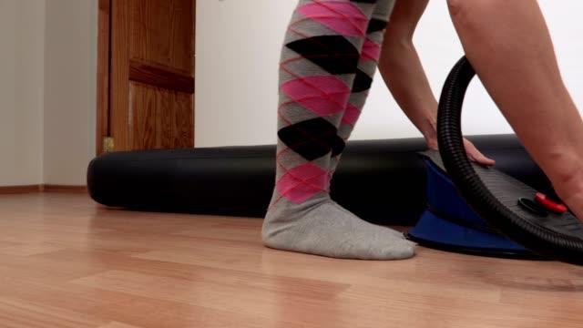 Woman bring pump and put near to the air mattress video