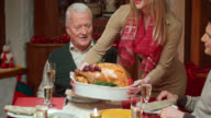 Woman bringing turkey to the Christmas table and  family applauds video