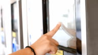 Woman buy the ticket by automatic ticket dispenser video