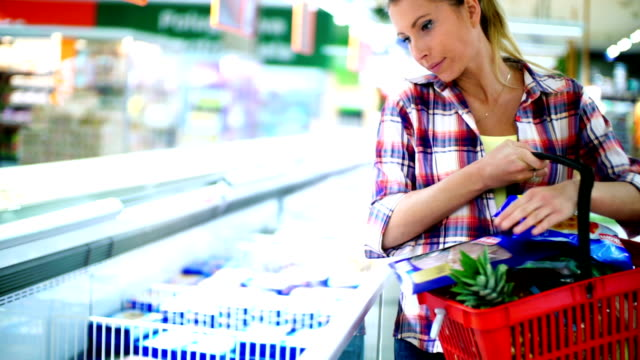 Woman buying some frozen food in supermarket. video