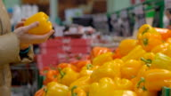 Woman buys a bell peppers in the store video