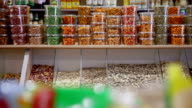 Woman buys jar of nuts and pistachios in grocery video