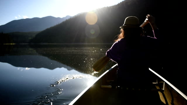 Woman canoeing on a pristine lake video
