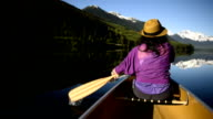 Woman canoeing on a pristine mountain lake video
