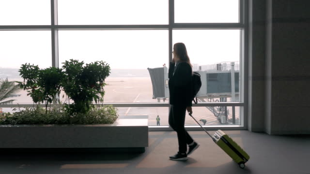 Woman chatting on mobile phone in airport terminal video