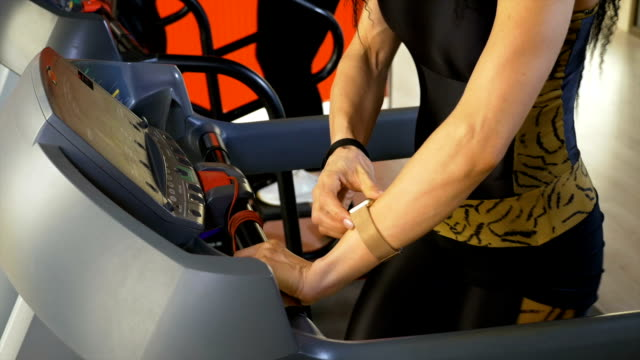 Woman checking heart rate on smartwatch during fitness exercise on treadmill video