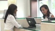 Woman Checking In At Hotel Reception Using Digital Tablet video