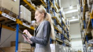 Woman checking supplies in the warehouse video