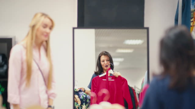Woman chooses a dress in a clothing store and consults with friend video