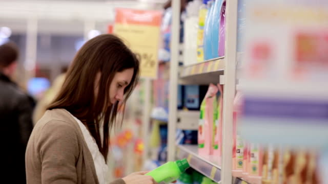 Woman chooses household chemicals in the store video