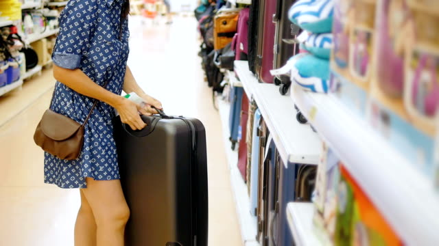 woman chooses suitcase at the supermarket video