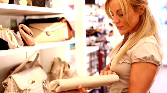 Woman choosing a purse. video