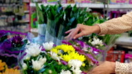 Woman choosing flowers in the shop video
