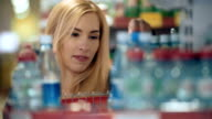 Woman choosing mineral water in grocery store video