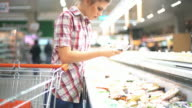 Woman choosing some food in supermarket. video