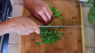 Woman chopping cilantro with a knife video