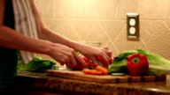 Woman chops vegetables for dinner salad. Home kitchen. video