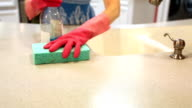 Woman cleaning her home kitchen using sponge, cleaning fluid. video