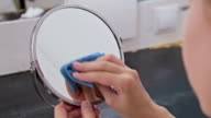 Woman cleaning mirror at home video