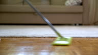 Woman cleaning parquet floors in the living room. Close-up video