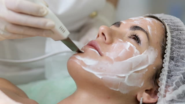 Woman cleaning skin on beautiful client face in beauty salon video