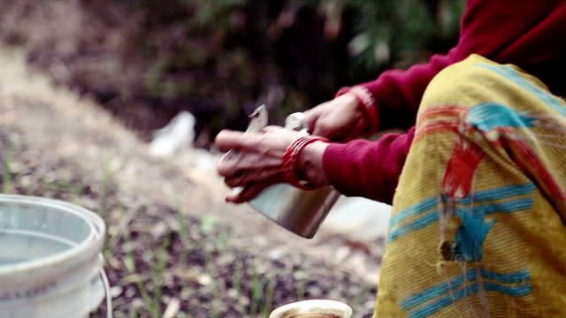 A woman cleaning utensils outdoor in hilly area of uttrakhand, India. video