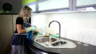 Woman cleans kitchen sink video