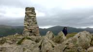 Woman climbing to mountain summit video