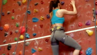 Woman climbing up rock wall video