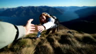Woman climbs mountain range, hand reach out to help video