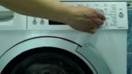 Woman closes the lid of the drum of the washing machine. A woman presses a buttons on the control panel. She is specifies a program of laundry washing and the washing machine starts to work. video