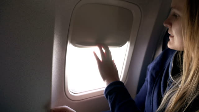 Woman closing blind in plane and using tablet PC video