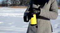 woman coat gloves open yellow thermos pour tea coffee winter video