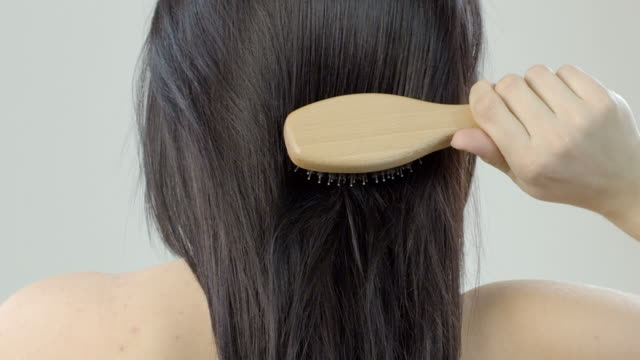 Woman combing her long hair with hairbrush video