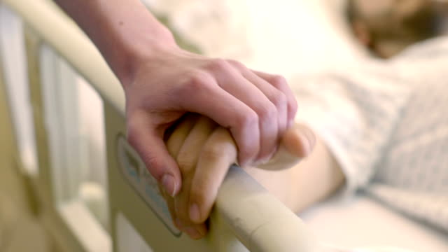 Woman Comforts Male Patient in Hospital Bed video