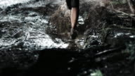 TD Woman competing in night trail run running across puddle video