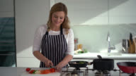 Woman cooking dinner at home video