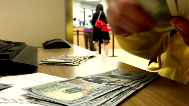 Woman counting US dollar inside HSBC bank video