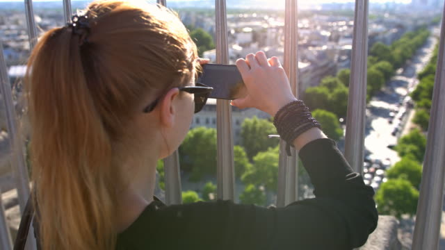 Woman creating memories by taking pictures of Paris from top of Arc de Triomphe video