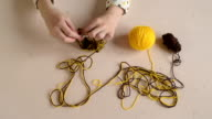 Woman crocheting yellow and brown yarn video