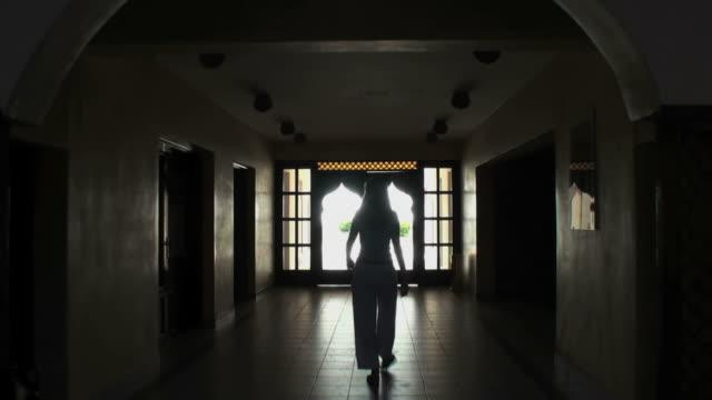 Woman (silhouette) crossing a dark arabian hall towards sunny exterior video
