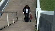 woman crutches stairs video