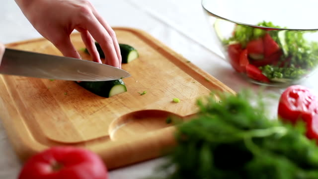 Woman cuts a cucumber salad. video