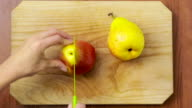woman cuts a pear on a wooden board. top view video