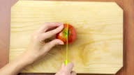 woman cuts a tomato on a wooden board. view from above. top view video