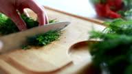 Woman cuts dill salad. video
