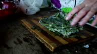 woman cuts frozen herbs video