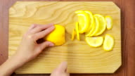 woman cuts lemon on a wooden board. view from above. top view video