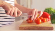 woman cuts tomato video