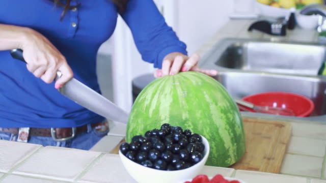 A Woman cutting and opening a Watermelon video
